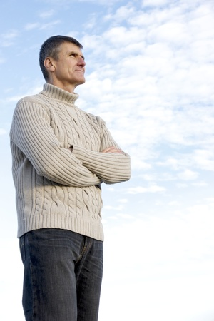greying: Fifty-year-old standing with hands crossed ponders future plans including his retirement options.