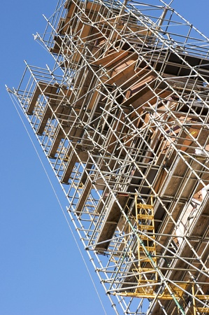 Commercial scaffolding surrounds a church spire under restoration.