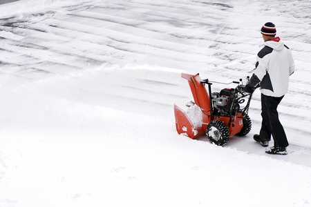 snow clearing: A man clears snow from a driveway with a snow thrower after a winter storm in Canada. Stock Photo