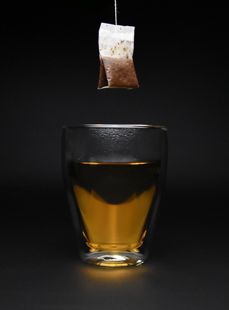 Cup of hot tea with tea bag black background
