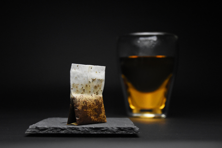 Cup of tea with tea bag on black background