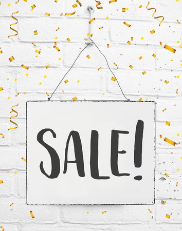 Sale sign text discount white sign banner board with golden confetti on white brick background