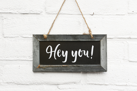 Empty chalkboard with space for own text hanging on white brick background