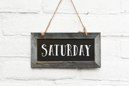 Hola texto de sábado en tablero colgante pared de ladrillo blanco ourdoor
