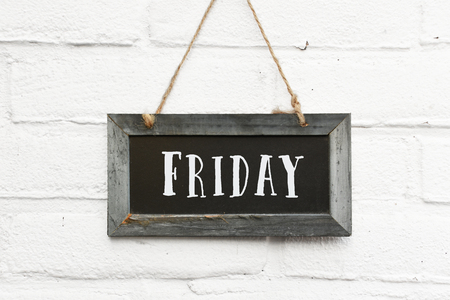 Hello friday text on hanging board white brick outdoor wall Banco de Imagens