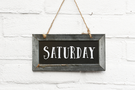 Hello saturday text on hanging board white brick outdoor wall Фото со стока