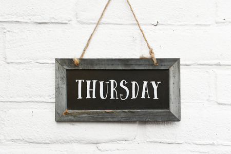 Hello thursday text on hanging board white brick outdoor wall