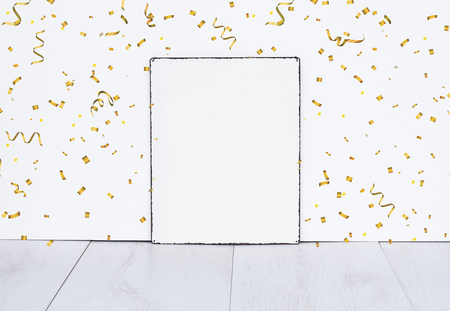 White empty board standing on grey wooden floor against white isolated wall with golden party confetti mock up for birthday or party