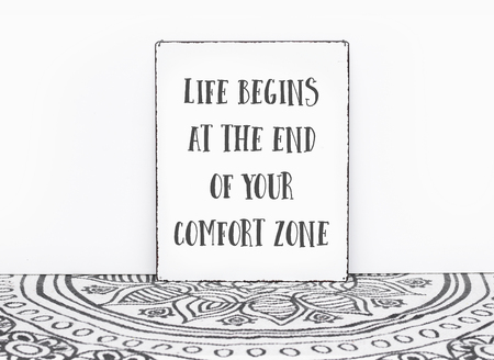 Bohemian vintage carpet travel quote life begins at the end of your comfort zone text on board white isolated wall background