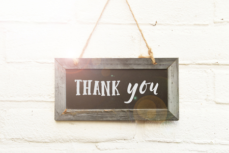 Thank you text handwritten typography on chalkboard hanging on white brick wall background