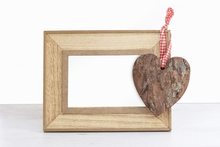 Emptty wooden photo frame with hanging heart shape bark standing on wooden table against white isolated wall