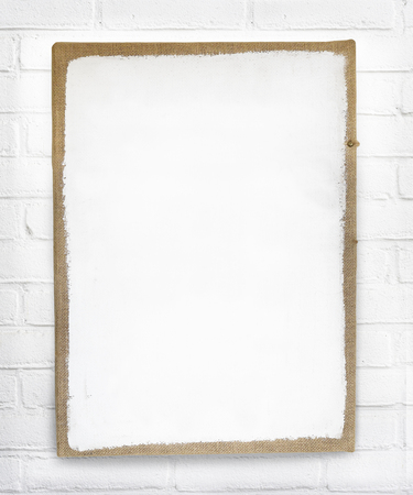 Mockup of white empty canvas photo frame with brown border hanging on white brick wall with space for own text