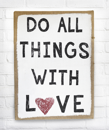 Text do all things with love positive quote on hanging board against white brick wall