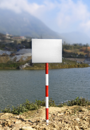 Mockup white empty warning sign by water on a travel holiday in the mountains