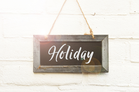 Holiday text quote on wooden sign board hanging on white brick wall