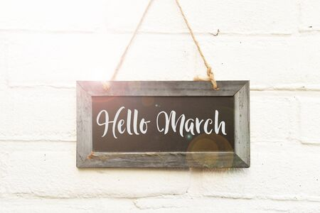 Handwritten text hello March on hanging black chalkboard againt white outdoor wall