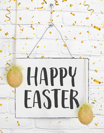 Happy easter text quote on sign board with confetti and eggs Easter decoration