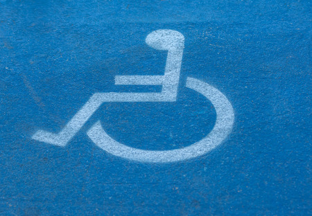 wheelchair access: blurred disabled,handicap sign on blue floor