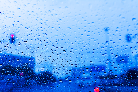 city scene: rain drops on window on road with blurred background