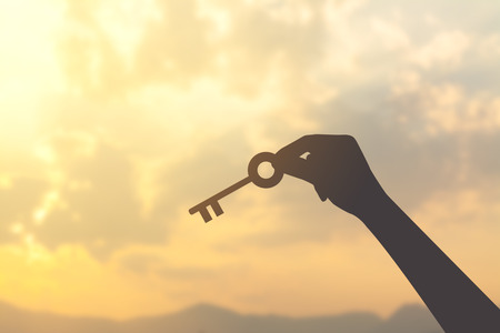 lock symbol: silhouette hand with key and sunrise background Stock Photo