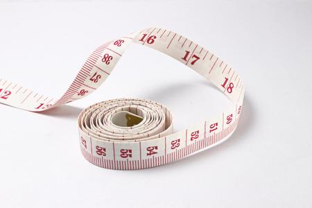 cinta de medir: Cinta métrica sobre fondo blanco