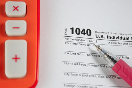 tax form: US tax form with pen and calculator selective focus  taxation concept