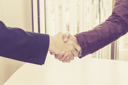The two businessmen shake hands after successfully doing business.
