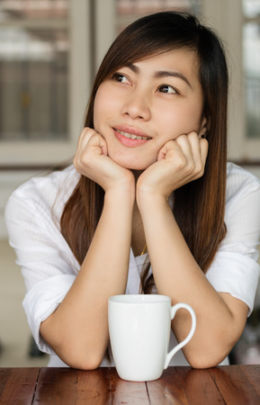 Asian woman smiling happily with drinking coffee in the morning.