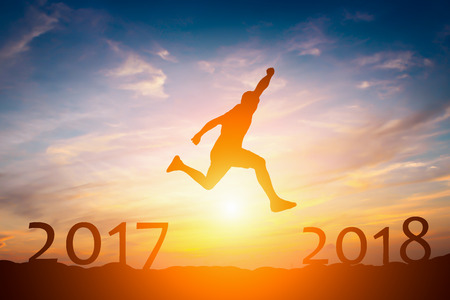 Silhouette of  man jump from 2017 to 2018 success concept in sunset
