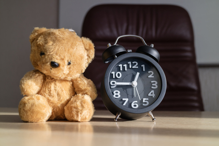 Alarm clocks and teddy bears placed on the a desk with sunshine in the afternoon  concept father and son.