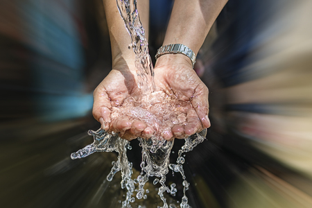 Spring water flows from the pipe into the hands