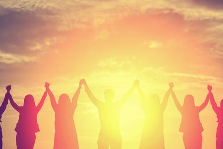 비즈니스 팀웍 개념에 대 한 일몰 하늘 배경에서 높은 손을 만드는 행복 한 비즈니스 팀의 실루엣