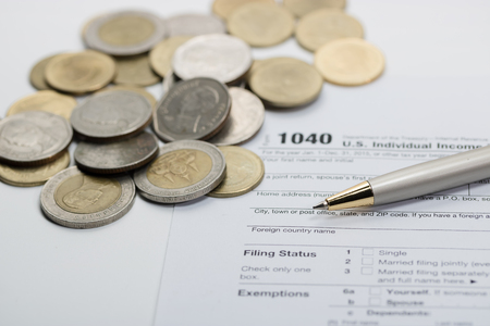 cpa: US tax form with pen and coins  selective focus  taxation concept