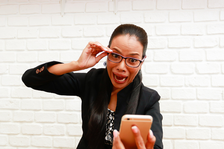 Businesswoman shocked with something in smartphone.