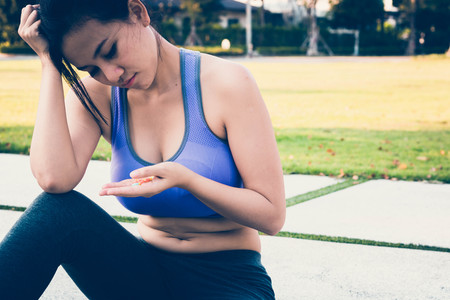 young women in sportswear falling lose consciousness on sidewalk trying to eat diet pills in hand Stock Photo