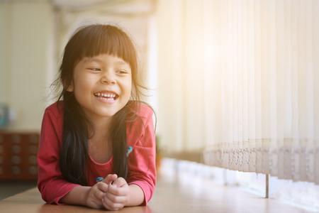 humor: Happy Asian girl playing side window. Stock Photo