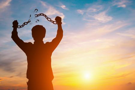Imagen de silueta de un hombre de negocios con cadenas rotas en puesta de sol