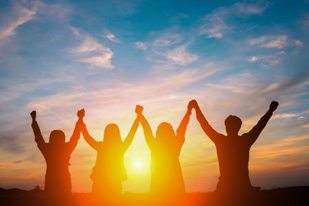 비즈니스 팀워크 개념에 대 한 도시 배경에서 높은 손을 만드는 행복 한 사업 팀의 실루엣