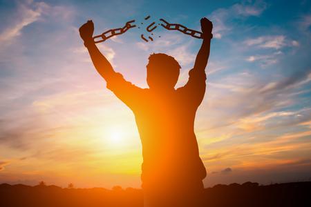 Imagen de silueta de un hombre de negocios con cadenas rotas en puesta de sol Foto de archivo - 87173291