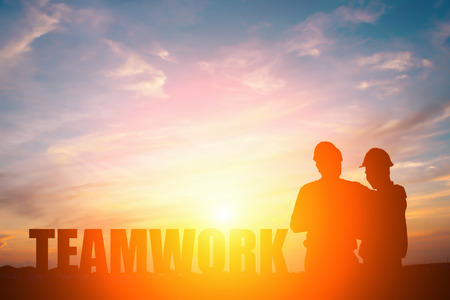 Silhouette of two engineers in sunset, teamwork concept. Stock Photo
