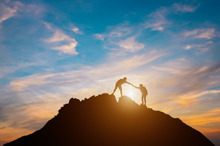 Silhouette of couple teamwork  hiker helping each other on top of mountain 免版税图像