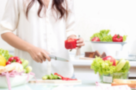 Blurred image of Young happy woman cutting vegetables in the kitchen.
