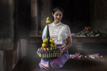 Beautiful Asian woman holding a Krathong sitting by the window. Loy Krathong Festival of Thailand National culture.Held annually at the end of the year.