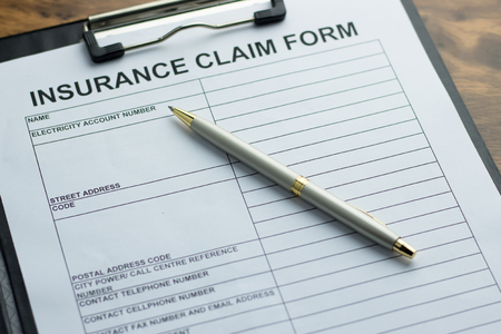 Insurance claim form with pen on  wooden table. selective focus