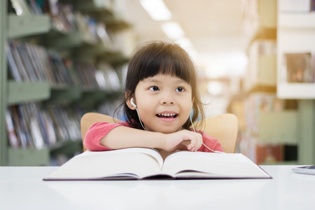 Asian girls are reading books and listening to music in the library happily. Stock Photo