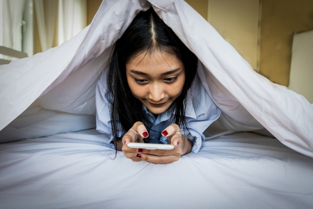 Asian woman using a smart phone in the bedroom.