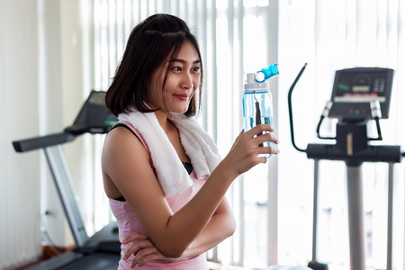 Beautiful healthy and happy woman are drinking water in the gym.After the exercise.