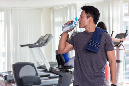Happy healthy man are drinking water in the gym.After the exercise. Stock Photo