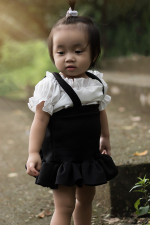 Happy Asian baby girl playing in the garden