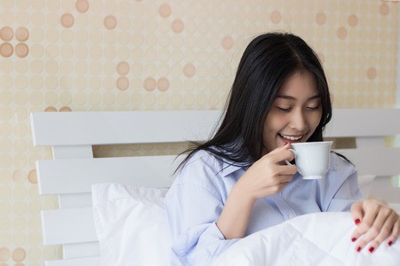 Happy Asian woman drinking coffee on bed